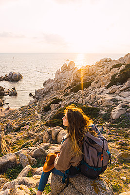Italy, Sardinia, woman on a hiking trip sitting on rock at the coast - p300m1580871 by Kike Arnaiz