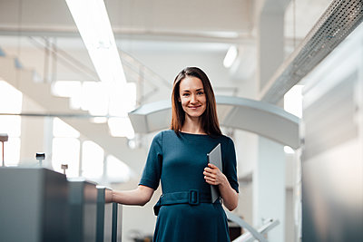 Smiling mid adult businesswoman standing with digital tablet in industry - p300m2299387 by Kniel Synnatzschke