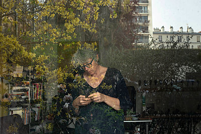 Grey-haired woman uses mobile phone in her apartment - p445m2173643 by Marie Docher