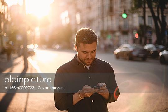 Happy man using smart phone standing on street in city in summer - p1166m2292723 by Cavan Images