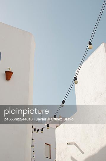 lighting in street of mediterranean town, wire with bulbs - p1656m2244810 by Javier Martinez Bravo