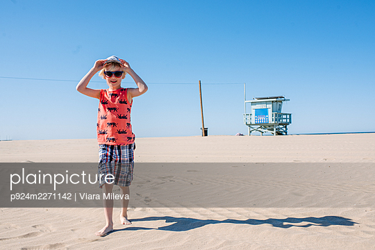 Boy on sunny sandy beach, wearing sunglasses and hat - p924m2271142 by Viara Mileva