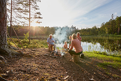 Grandparents and grandchildren enjoying campfire at sunny lakeside in woods - p1023m1172716 by Francis Pictures