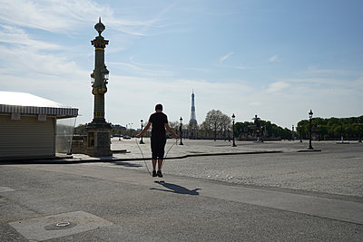 A young man plays with a skipping rope in place Concorde with Eiffel tower - p1610m2181487 by myriam tirler
