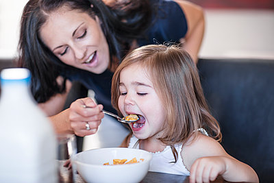 Mother feeding daughter breakfast cereal at table - p300m1416455 by zerocreatives