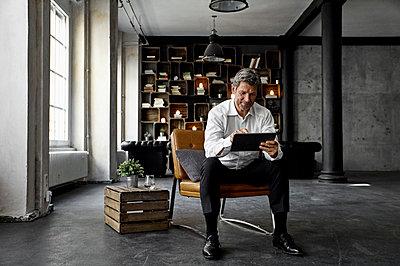 Smiling mature man using digital tablet in loft - p300m1581409 von Philipp Dimitri
