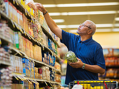 African American man shopping in grocery store - p555m1453317 by Erik Isakson