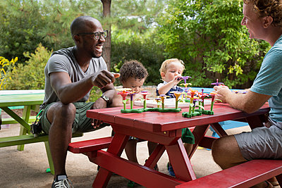Fathers and toddler sons playing at picnic table - p555m1459367 by Roberto Westbrook