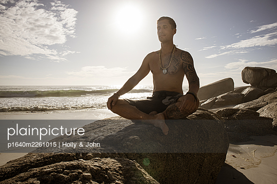 Man practises meditation on the beach in the sunshine - p1640m2261015 by Holly & John
