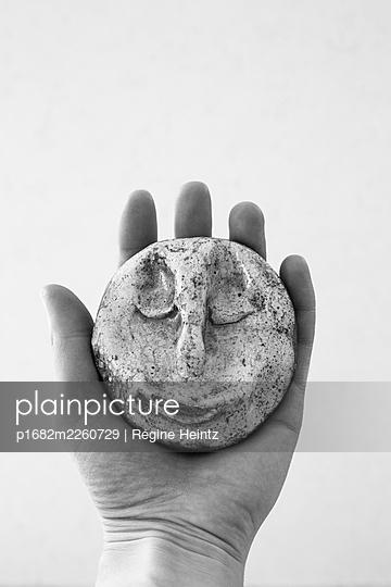 Hand holding a moon-shaped ceramic - p1682m2260729 by Régine Heintz