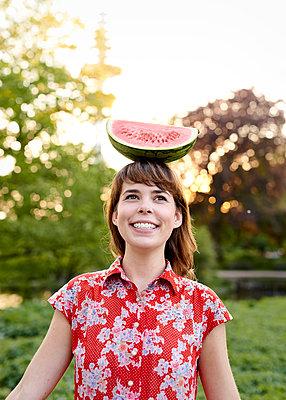 Frau balanciert Wassermelone auf dem Kopf - p1124m1134796 von Willing-Holtz