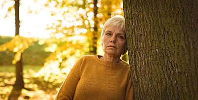 Thoughtful senior woman leaning on tree trunk in the park on a sunny day - p1315m1565687 by Wavebreak