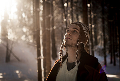 Young man with knit hat in a forest - p1324m1165215 by Michael Hopf