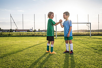 Smiling young football players shaking hands on football ground - p300m1581170 von Fotoagentur WESTEND61