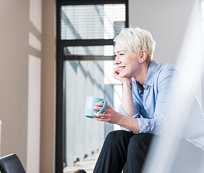 Smiling woman with cup of coffee sitting on table in office - p300m1581706 by Uwe Umstätter