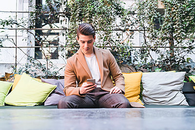 Young man sitting on couch in a cafe using cell phone - p300m2102922 by Francesco Buttitta