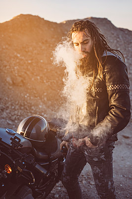 Portrait of bearded biker with dreadlocks  smoking electronic cigarette - p300m2104519 by Oscar Carrascosa Martinez