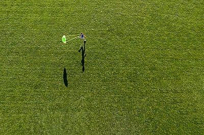 Aerial view of a running woman with a parachute on lawn - p300m2132528 by Stefan Schurr