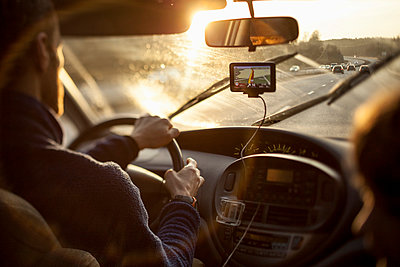 Cropped image of man driving car while using GPS by daughter - p426m958766f by Katja Kircher