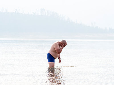 Senior man standing thigh deep in water, washing his face. Heat and smoke haze in the air from bush fires.  - p924m2165120 by Elke Meitzel