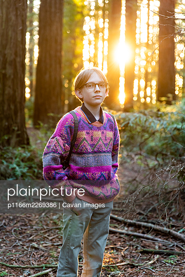 Portrait of young person standing in forest with sun setting - p1166m2269386 by Cavan Images