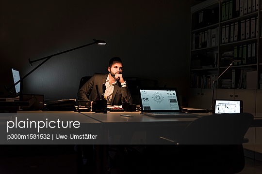 Pensive businessman sitting at desk in office at night - p300m1581532 von Uwe Umstätter