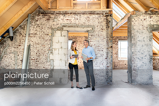 Businesswoman having discussion with expertise while standing at construction site - p300m2256450 by Peter Scholl
