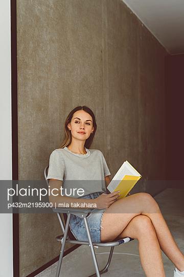 Junge Frau liest entspannt ein Buch - p432m2195900 von mia takahara