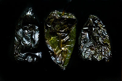 Three charred Poblano peppers against a black background - p1166m2130722 by Cavan Images