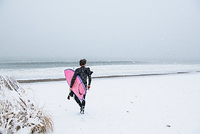 Man going surfing during winter snow - p1166m2177087 by Cavan Images