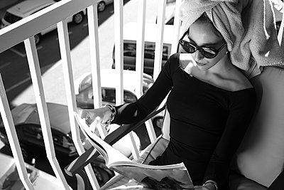 Glamour lady reading a magazine on balcony - p300m2132294 by DREAMSTOCK1982