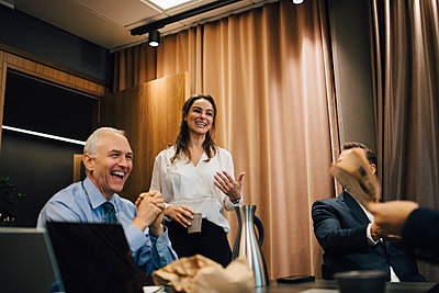 Smiling business people discussing in board room at office - p426m2270842 by Maskot