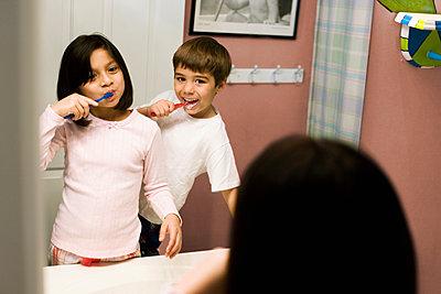 Hispanic children brushing their teeth - p555m1454150 by Jon Feingersh
