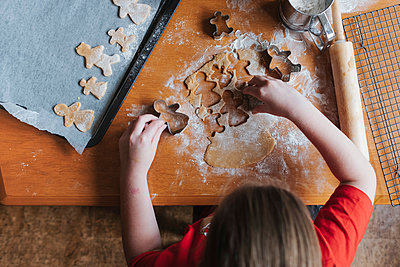 Overhead view of a girl using cookie cutters to make gingerbread man - p1166m2212773 by Cavan Images