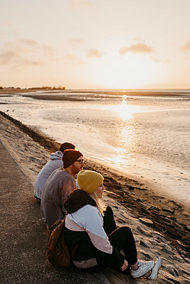 Namibia, Walvis Bay, three friends relaxing at sunset - p300m2080825 von letizia haessig photography