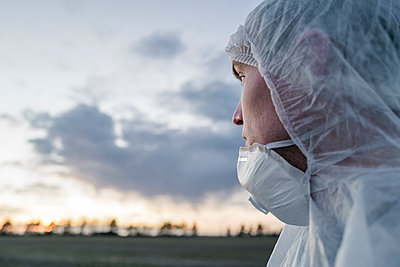 Portrait of man wearing protective suit and mask looking at sunset - p300m2170144 by Ekaterina Yakunina