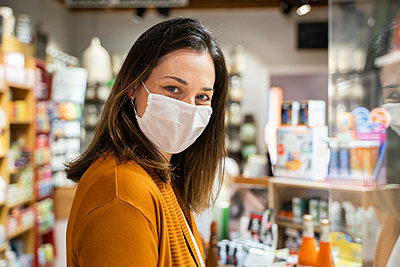 Young woman wearing protective face mask standing in grocery store during pandemic - p300m2264485 by VITTA GALLERY