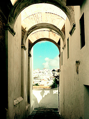 View through arched alleyway to hillside community, Spain - p349m2167736 by Polly Wreford