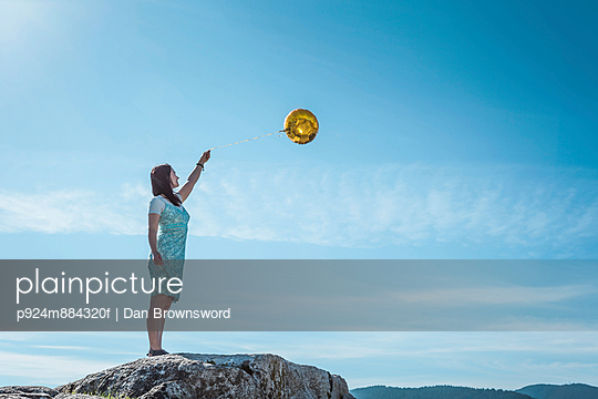 Mature woman standing on rock with golden balloon - p924m884320f by Dan Brownsword