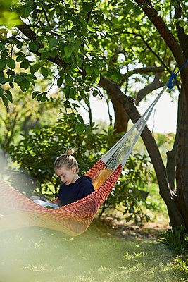 Girl in hammock reading a book - p300m2199259 by Maya Claussen
