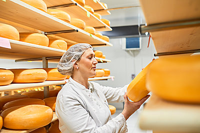 Cheese factory, female worker with cheese wheel in storeroom - p300m2199674 by Zeljko Dangubic