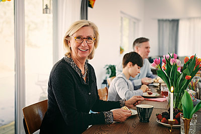Portrait of smiling grandmother sitting with family at table during party - p426m1580209 by Maskot