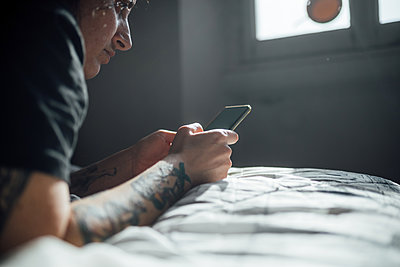 Woman with tattooed arm lying on bed, using mobile phone during Corona virus crisis. - p429m2183107 by Eugenio Marongiu