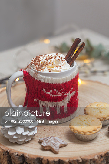 Christmas, mince pies and mug of hot chocolate or eggnog with a knitted wraparound cover - p1100m2300980 by Mint Images