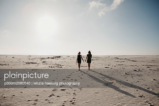 South Africa, Western Cape, Noordhoek Beach, back view of two young women strolling on the beach - p300m2080840 by letizia haessig photography