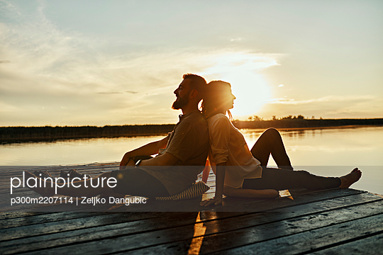 Couple sitting back to back on jetty at a lake at sunset - p300m2207114 by Zeljko Dangubic
