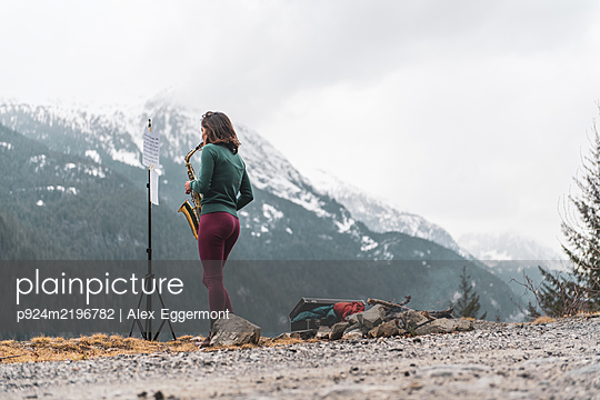 Woman standing on a mountain in the Squamish Valley, British Columbia, Canada, playing the saxophone. - p924m2196782 by Alex Eggermont
