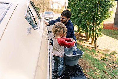 A father and his toddler daughter washing a classic car together. - p1166m2190679 by Cavan Images