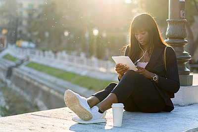 Businesswoman sitting outdoors using a digital tablet - p300m2140457 by Giorgio Fochesato