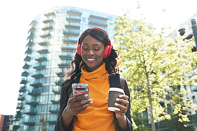 Smiling female professional with disposable coffee cup listening music at office park - p300m2241591 by Pete Muller